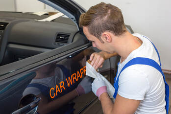 Picture showing a wrap installer applying letters on a car